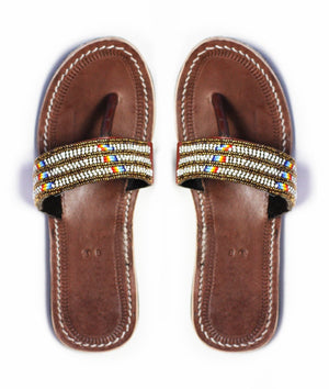 A pair of meaningful gold and white Kenyan beaded leather sandals, the Pwani  sandal, on a white background