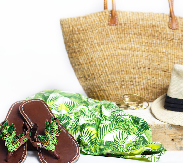 Green Kenyan beaded leather sandals with a beaded leaf design in a staged beachy scene