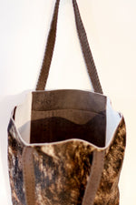 The inside pocket of a purposeful brindle cowhide tote bag with brown handles that makes a difference