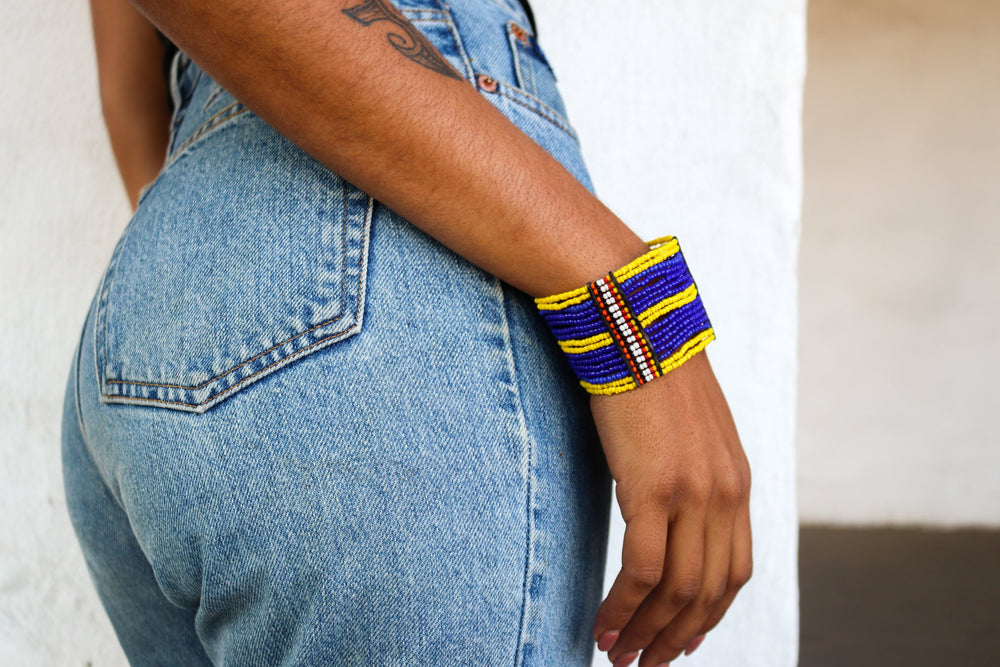 An ethical blue and yellow cuff on a model