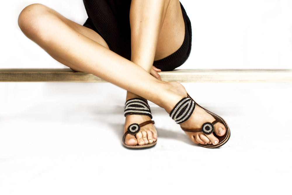 A pair of black and white handmade African beaded leather sandals, the Rafiki sandal, on a model