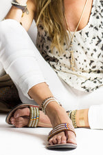 A pair of gold and white ethical African beaded leather sandals, the Pwani sandal, on a model