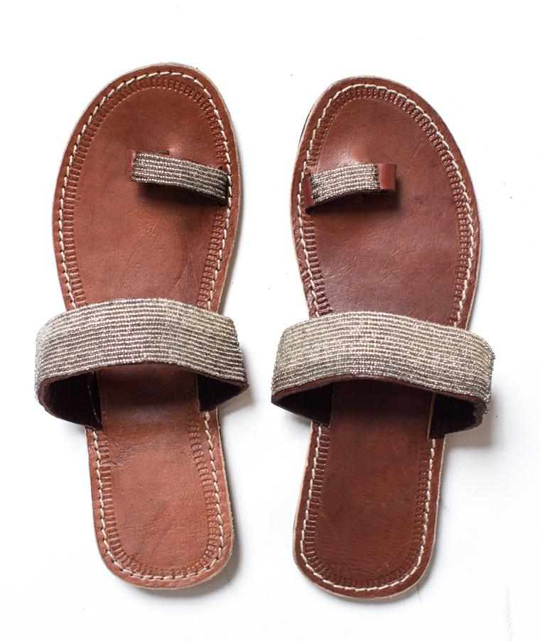 A pair of meaningful silver Kenyan beaded leather sandals, the Mkali sandal, on a white background