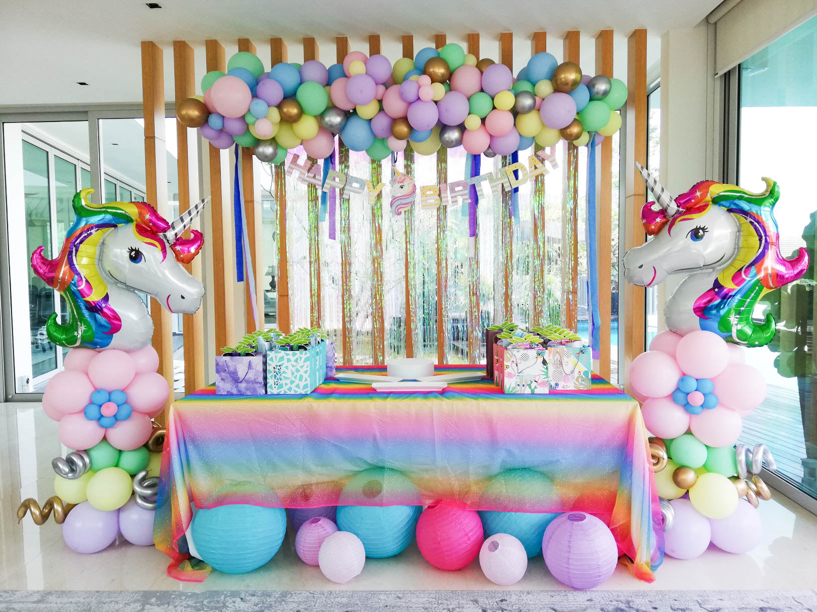 beautiful unicorn themed table decorations with mini balloon garland, happy birthday letter and lanterns. 2 big unicorn foil balloons by the side of the table.