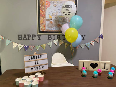 children birthday with colorful balloon bouquets and birthday banners, table are setup with wording sign and cups.