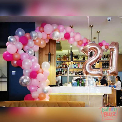 Organic Balloon Arch in Pink and 2 Gold Foil Numbers decorated by the side of the restaurant.