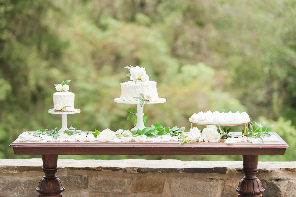 white wedding cakes on cake table with tips for planning wedding during holidays - The Garter Girl