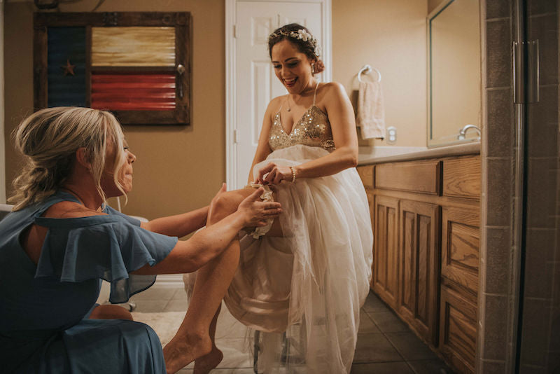 bride and bridesmaid putting on wedding garter
