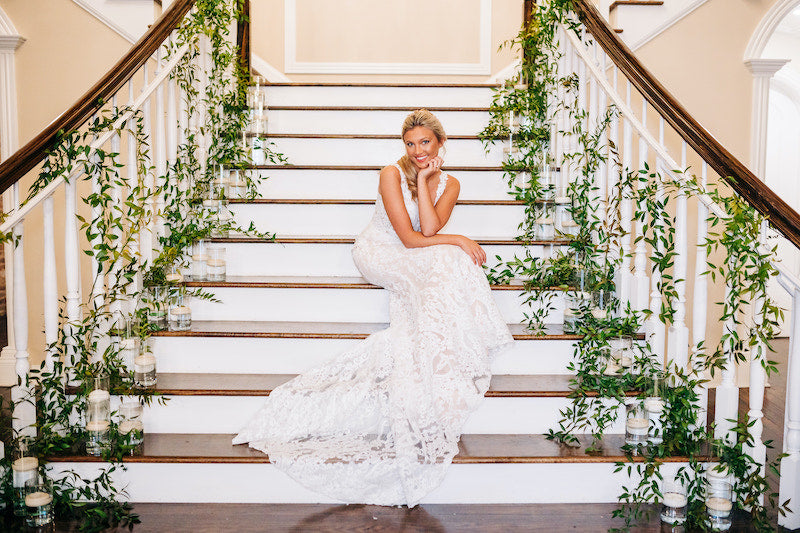 Bride Posing on Staircase with Wedding Flowers