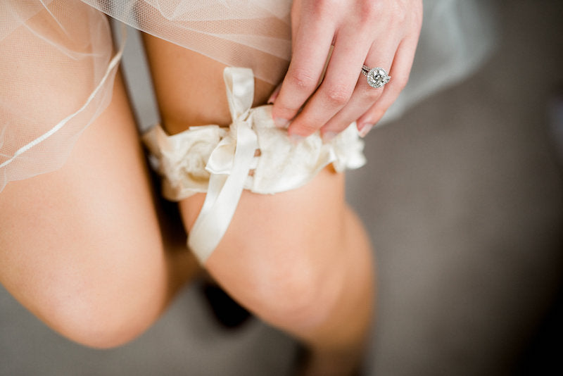 bride putting on elegant garter