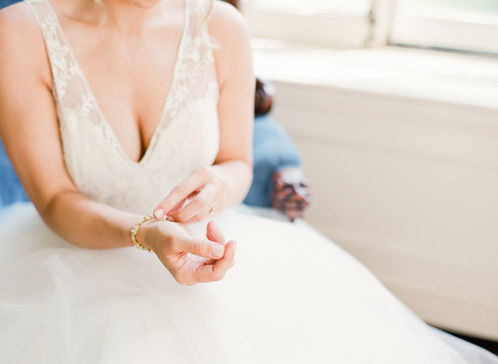 bride getting dressed - tips about trying wedding dresses on at home from The Garter Girl