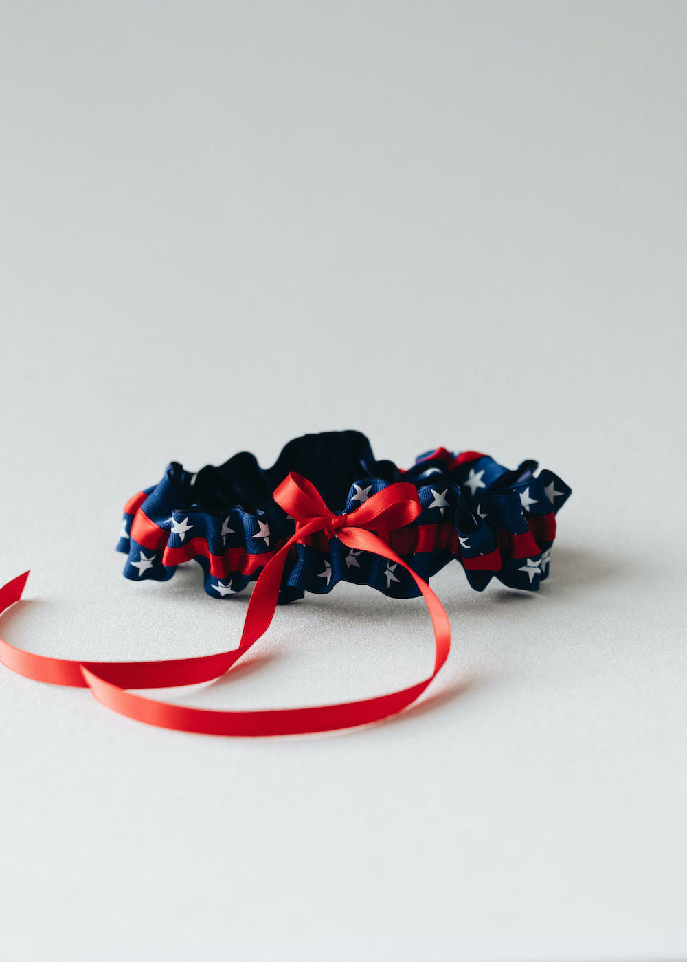 patriotic usa themed, red, white & blue wedding garter set personalized with couple's names and wedding date handmade bridal accessory by The Garter Girl