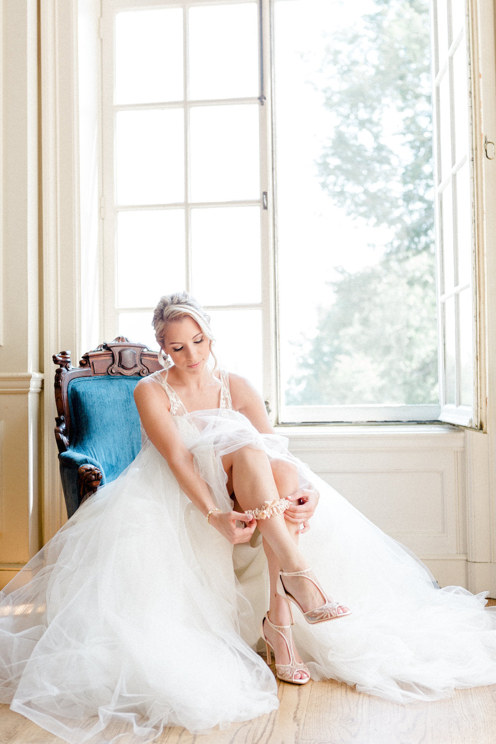 bride putting on garter - tips about trying wedding dresses on at home from The Garter Girl