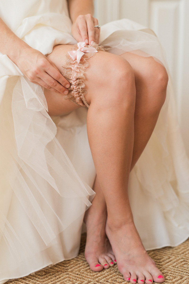 bride putting on wedding garter