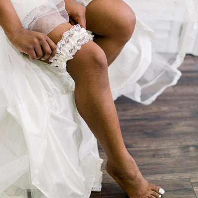 Shop our heirloom wedding garter with floral ivory lace and satin bow.