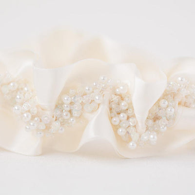 Shop our heirloom bridal garter with faux pearls, beads and ivory satin.