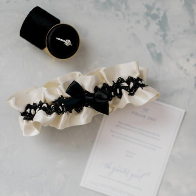 Shop our heirloom black lace wedding garter featuring black satin.