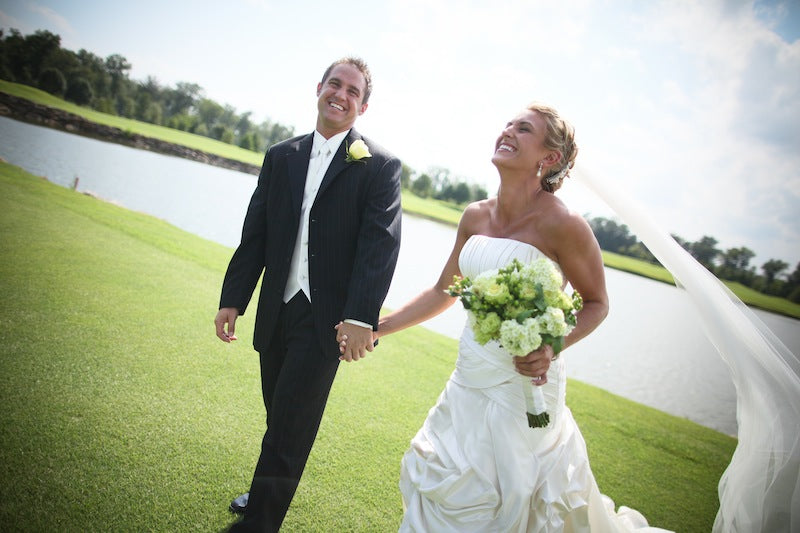 bride and groom walking through golf course
