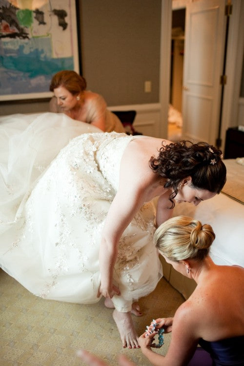 bride-putting-on-beautiful-garter-photo-by-paul-morse