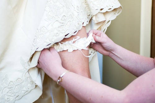 bride-putting-on-beautiful-wedding-garter-The-Garter-Girl-by-Julianne-Smith-photo-credit-Missy-Photography