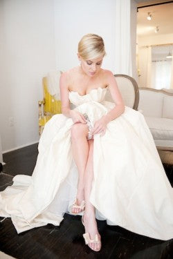 bride-putting-on-gorgeous-garter-The-Garter-Girl-by-Julianne-Smith-photo-by-missy-photography