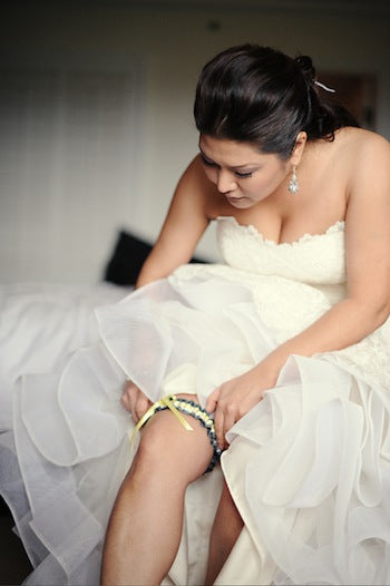 bride-putting-on-gorgeous-wedding-garter-The-Garter-Girl-by-Julianne-Smith-photo-by-hazelnut-photography