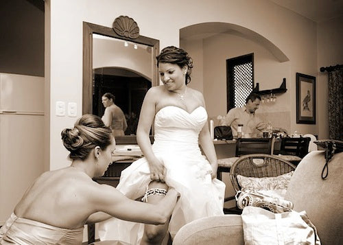 bride-putting-on-unique-polka-dot-wedding-garter-The-Garter-Girl-by-Julianne-Smith-photo-by-Eduardo-Lopez-Photography