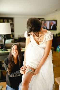 bride-putting-on-wedding-garter-The-Garter-Girl-Kaylee-Casanova-Photography