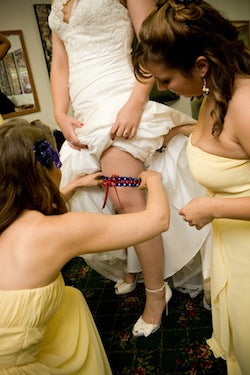 bridesmaids-helping-bride-with-wedding-garter-The-Garter-Girl-by-Julianne-Smith-Photo-credit-Tiffany-Atlas