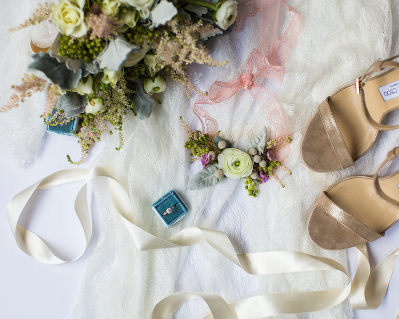 a collection of the bride's accessories and a fresh flower wedding garter