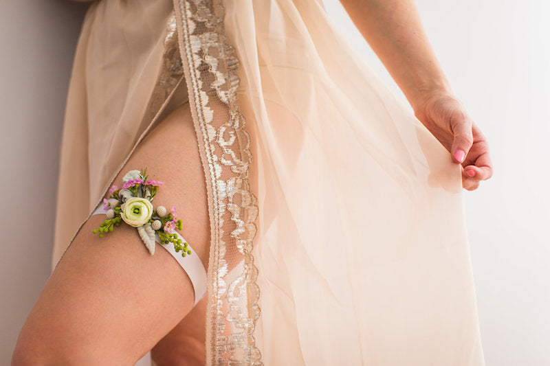 bride in lace robe and fresh flower wedding garter