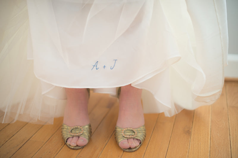 initials sewn on inside of wedding dress with gold bridal shoes