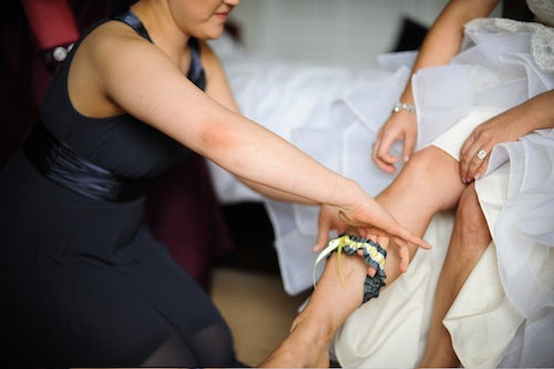 putting-on-stylish-wedding-garter-The-Garter-Girl-by-Julianne-Smith-photo-by-hazelnut-photography
