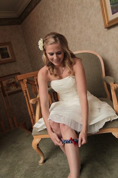 real-bride-putting-on-designer-wedding-garter-tiffany-wayne-photography