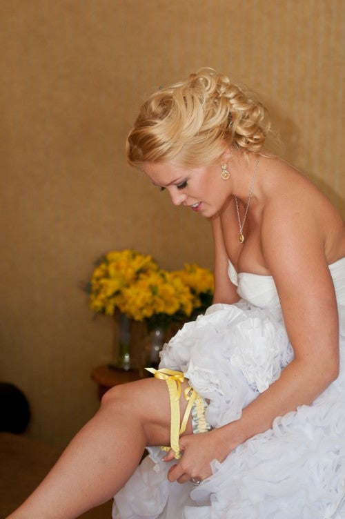 real-bride-putting-on-stylish-wedding-garter-The-Garter-Girl