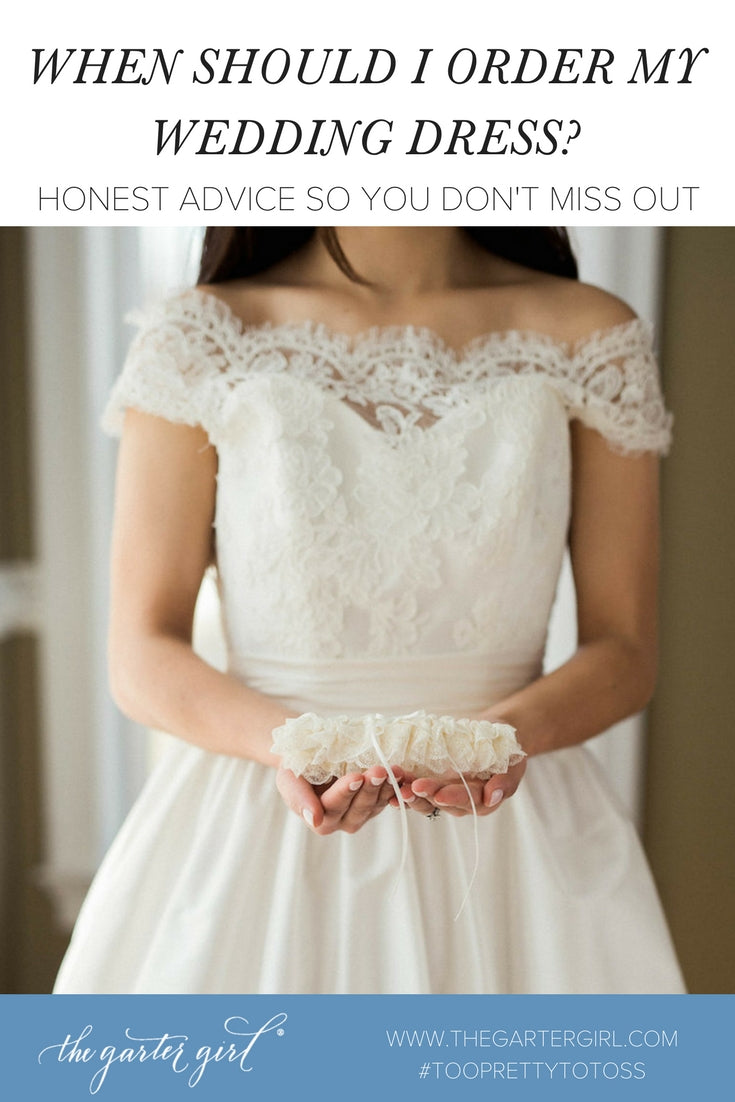 bride holding lace wedding garter - when to order wedding dress advice