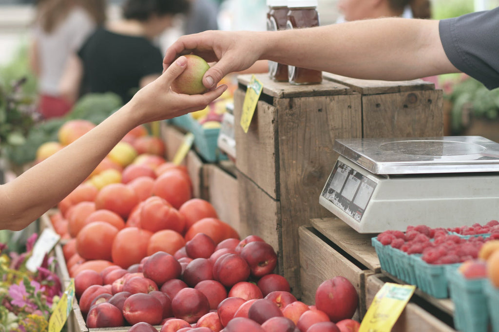 Close-up of a fresh piece of fruit being given from one person to another at a market