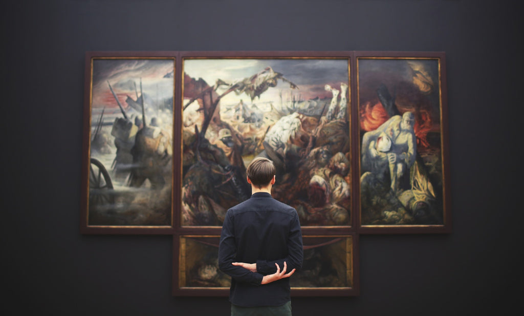Back of man looking at painting in a museum