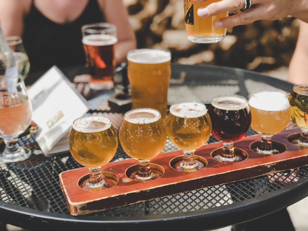 Glasses of beer on a tasting tray placed on an outdoor table