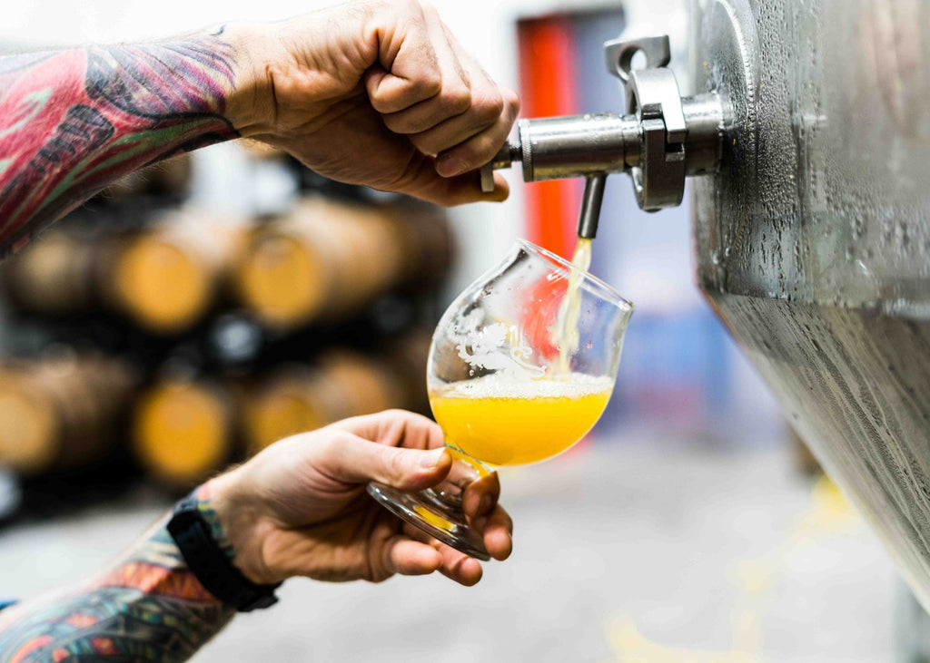 Close-up of hands pouring a glass of beer from a tap