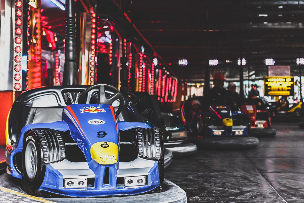 Bumper car parked with lights and people in the background