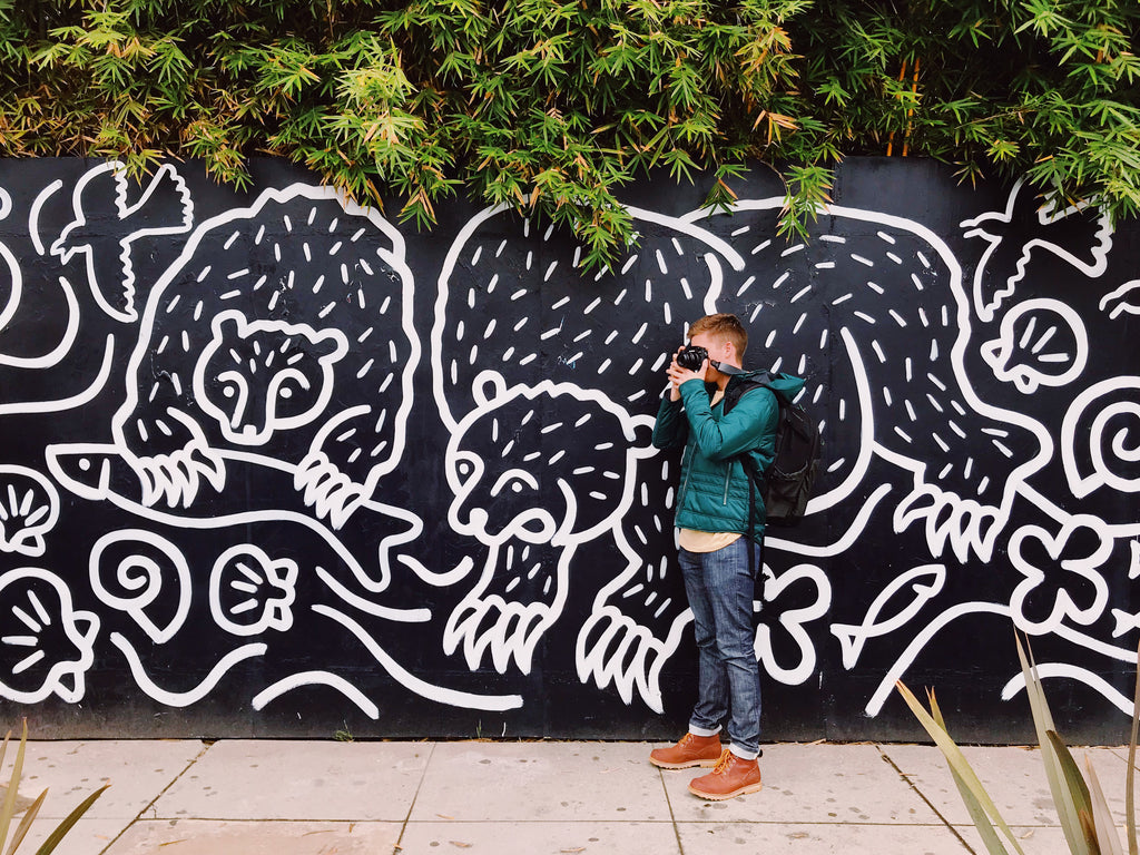 Man taking a photo in front of a wall with graffiti