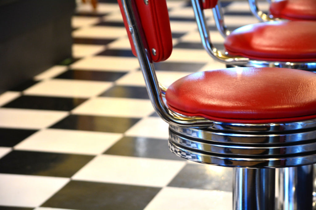 Close-up of vintage diner chair with red cushion and black and white checkered floor tiles