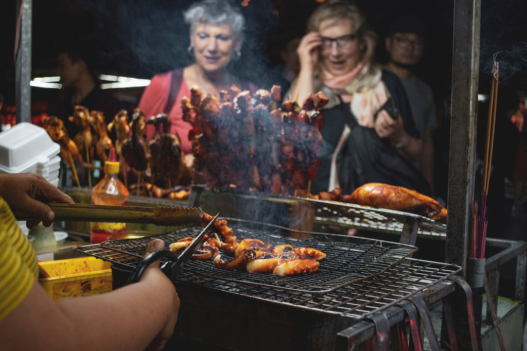 Man grilling food in front of onlookers