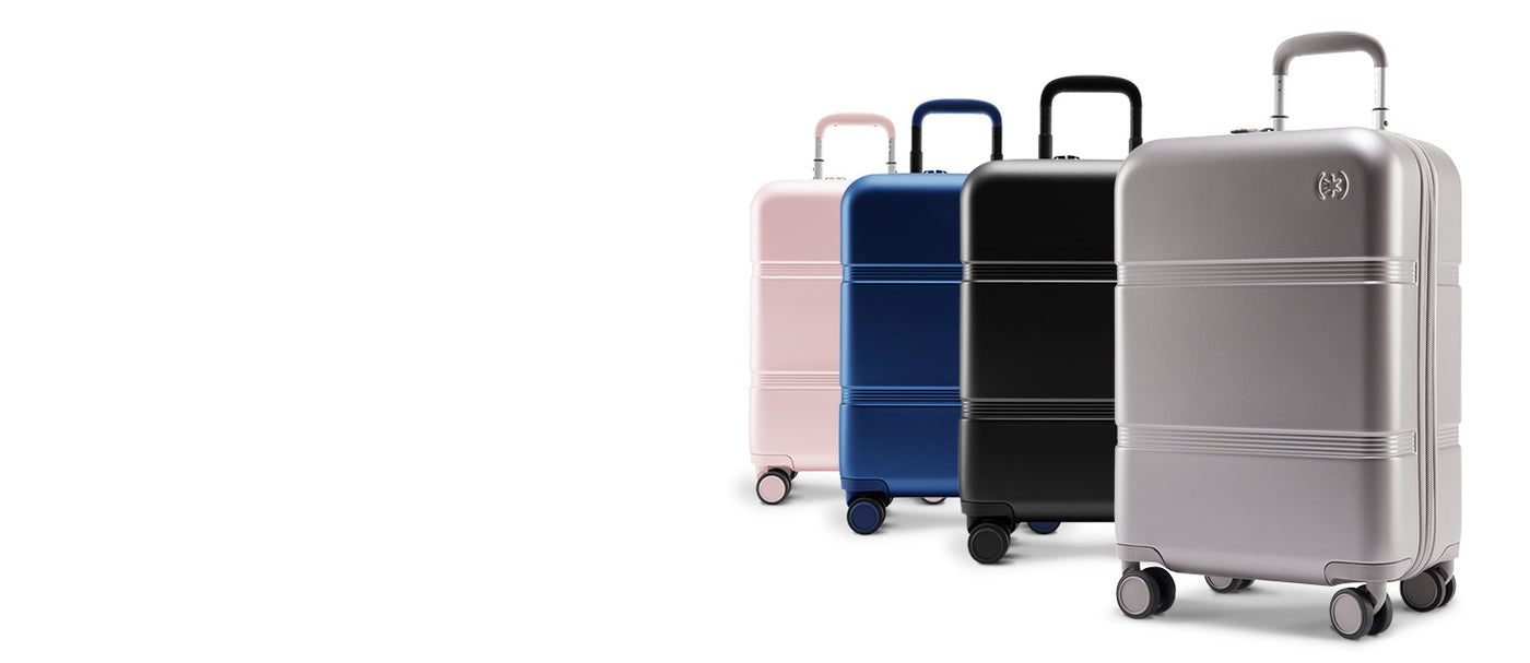 Four 22-inch Carry-On bags by Speck Travel lined up - Concrete Grey, Black, Macaw Blue, and Hyacinth Pink