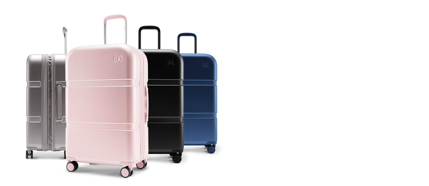 Four 26-inch Upright hardshell luggage bags by Speck Travel lined up - Hyacinth Pink, Black, Macaw Blue, and Concrete Grey