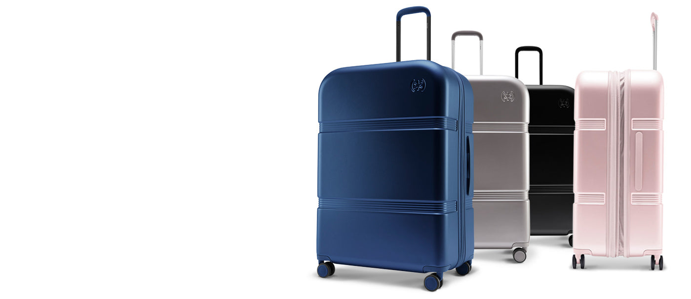 Four 29-inch Upright hardshell luggage bags by Speck Travel lined up - Macaw Blue, Concrete Grey, Black, and Hyacinth Pink