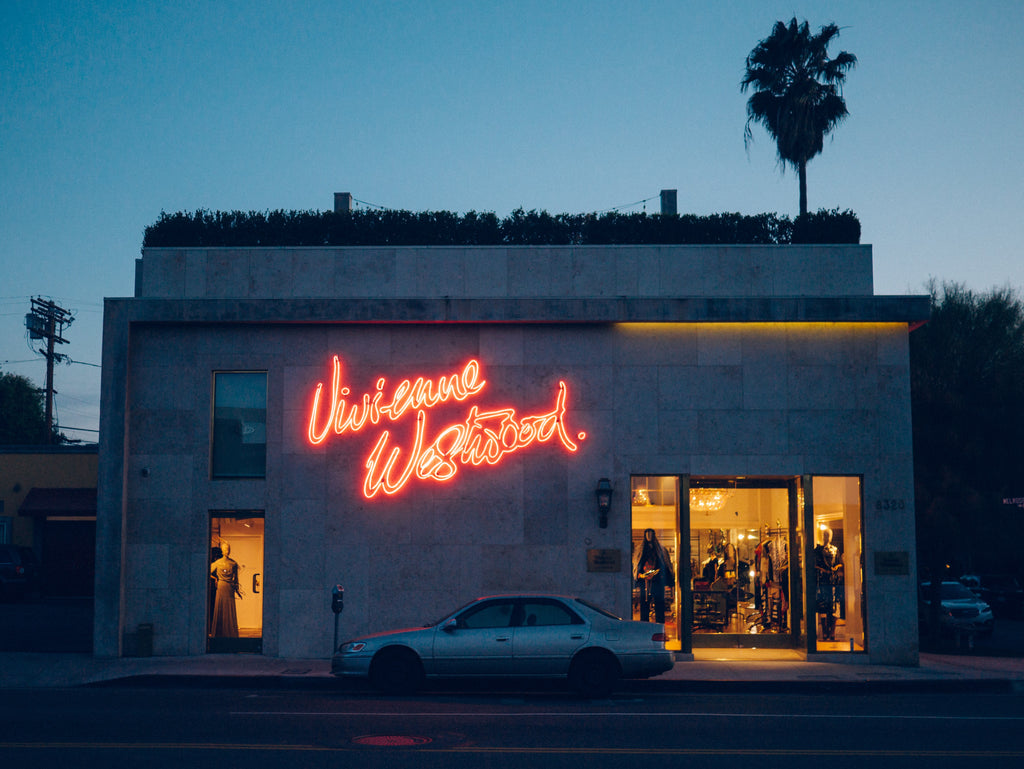 Car parked in front of building with neon sign at dusk