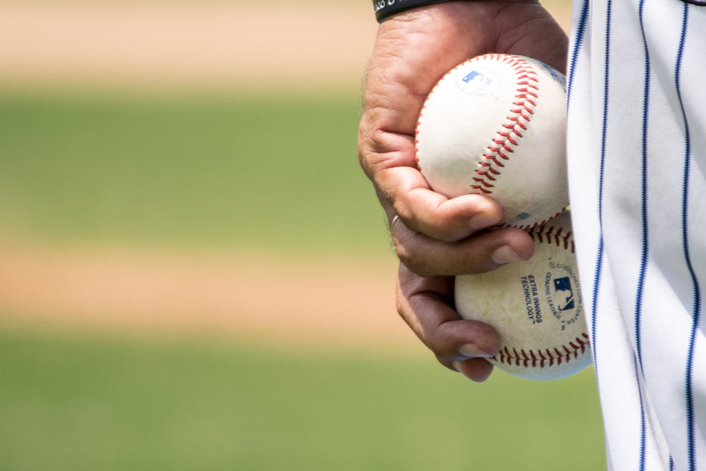 Close-up of a baseball player's hand holding two baseballs
