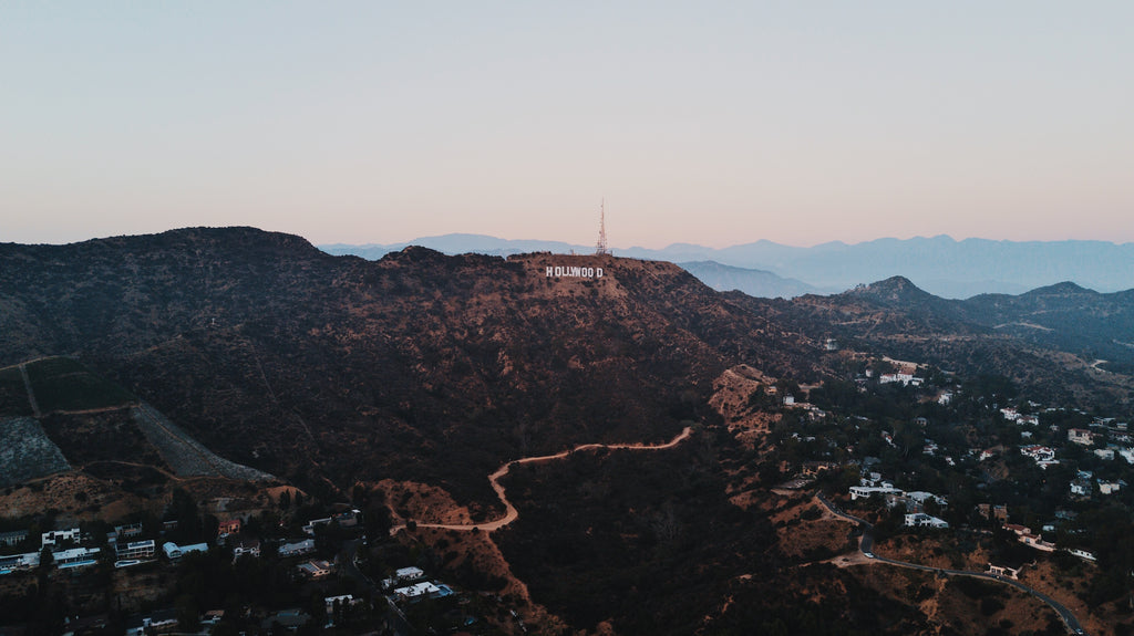 Aerial view of Hollywood sign along a mountain with homes below